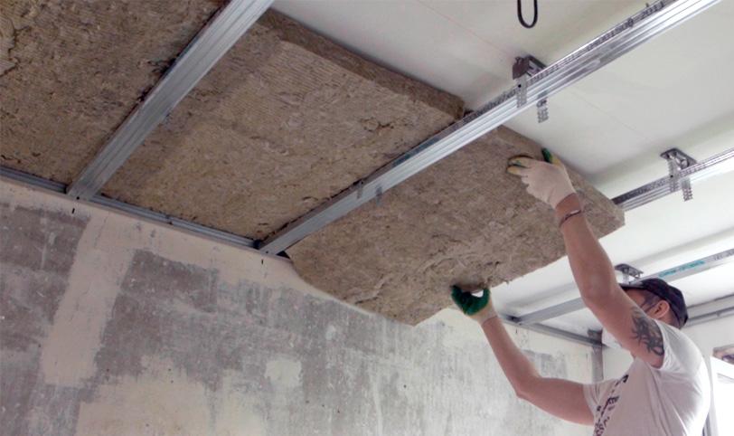 укладка наполнителя для шумоизоляции натяжного потолка