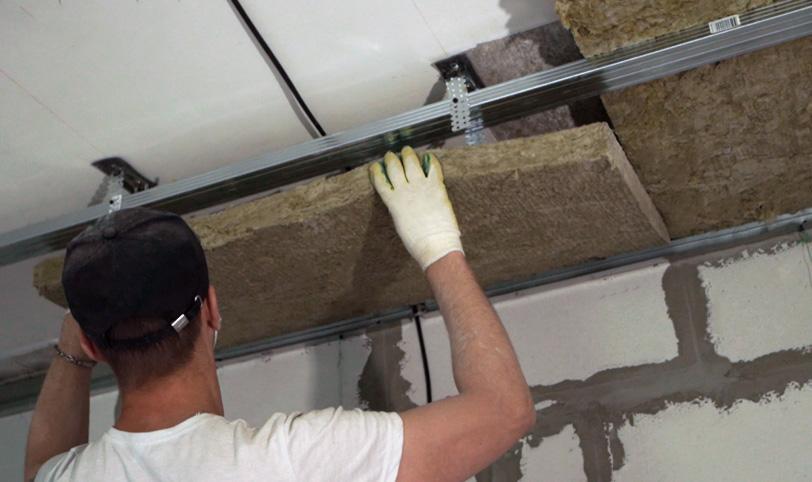 укладка волокнистого материала для звукоизоляции потолка